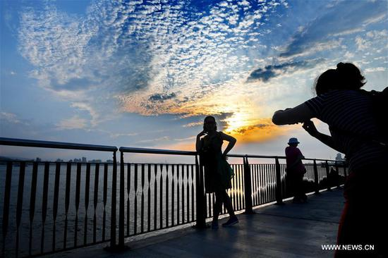 A tourist poses for photo by the Tamsui River at sunset in southeast China's Taiwan, April 25, 2019. (Xinhua/Zhang Guojun)