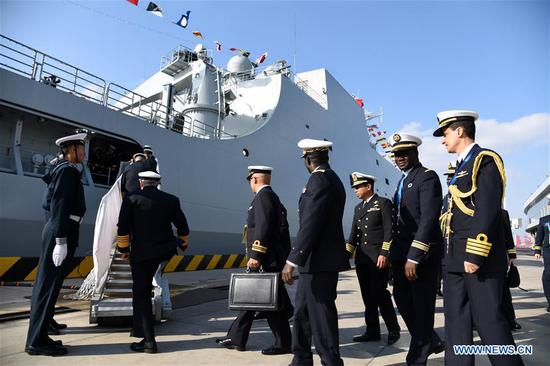 Foreign delegates prepare to visit the landing vessel Jinggangshan of the Chinese People's Liberation Army (PLA) Navy in Qingdao, east China's Shandong Province, April 25, 2019. Foreign delegations invited to participate in the multinational naval events marking the 70th anniversary of the founding of the Chinese PLA Navy visited Chinese vessels and communicated with Chinese soldiers and officers on Thursday. (Xinhua/Li Ziheng)