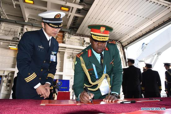 A foreign delegate signs a guest book during his visit to the landing vessel Jinggangshan of the Chinese People's Liberation Army (PLA) Navy in Qingdao, east China's Shandong Province, April 25, 2019. Foreign delegations invited to participate in the multinational naval events marking the 70th anniversary of the founding of the Chinese PLA Navy visited Chinese vessels and communicated with Chinese soldiers and officers on Thursday. (Xinhua/Li Ziheng)