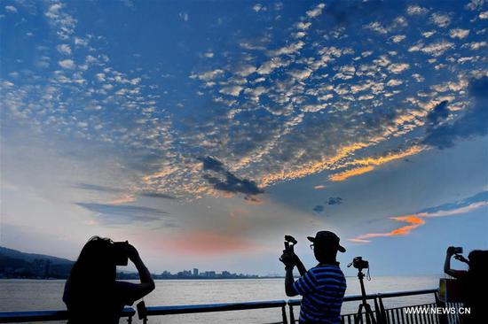 People take pictures of the Tamsui River at sunset in southeast China's Taiwan, April 25, 2019. (Xinhua/Zhang Guojun)