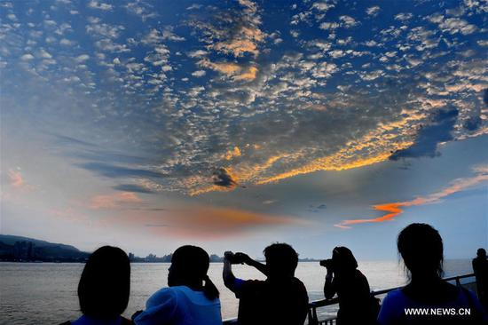 People view the Tamsui River at sunset in southeast China's Taiwan, April 25, 2019. (Xinhua/Zhang Guojun)
