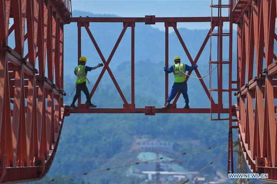 Workers Zhong Qi (L) and Feng Zhuang examine the Monei River bridge of the China-Laos railway in Pu'er City, southwest China's Yunnan Province, April 12, 2019. Linking Yuxi City in Yunnan and the Lao capital Vientiane, the China-Laos railway is expected to be fully operational by the end of 2021. (Xinhua/Qin Qing)