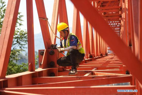 A worker fastens a screw at the construction site of the Monei River bridge of the China-Laos railway in Pu'er City, southwest China's Yunnan Province, April 12, 2019. Linking Yuxi City in Yunnan and the Lao capital Vientiane, the China-Laos railway is expected to be fully operational by the end of 2021. (Xinhua/Qin Qing)