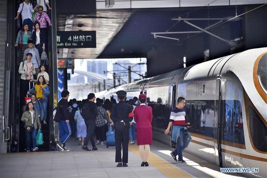 Passengers board a train at Tianjin Railway Station in north China's Tianjin, May 1, 2019. China's railway system saw a rise in passenger numbers as the four-day Labor Day national holiday began on May 1. (Xinhua/Yang Baosen)