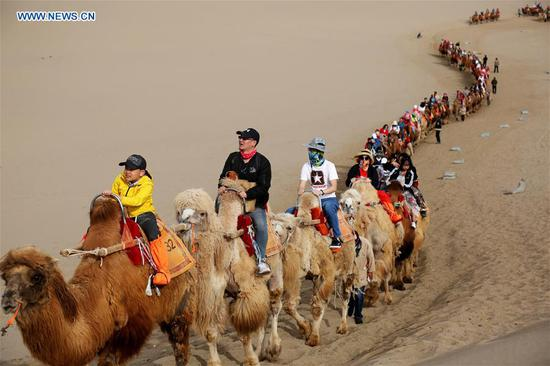 Tourists ride camels at the Mingsha Mountain and Crescent Spring scenic area in Dunhuang, northwest China's Gansu Province, May 2, 2019. (Xinhua/Zhang Xiaoliang)