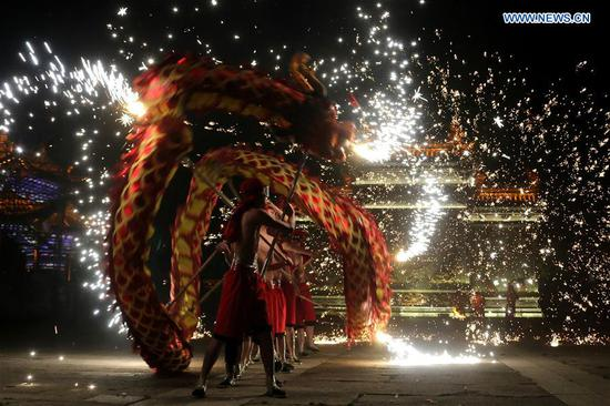 Performers spray molten iron to entertain visitors during the May Day holiday at the ancient town of Taierzhuang in Zaozhuang City, east China's Shandong Province, May 2, 2019. (Xinhua/Sun Zhongzhe)