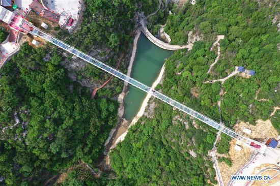 Aerial photo taken on May 3, 2019 shows tourists walking on a glass bridge in the Changshou Mountain scenic spot in Zhulin Township of Gongyi, central China's Henan Province. In recent years, Zhulin Township has been committed to developing tourism industry, as a way to boost people's income. (Xinhua/Feng Dapeng)