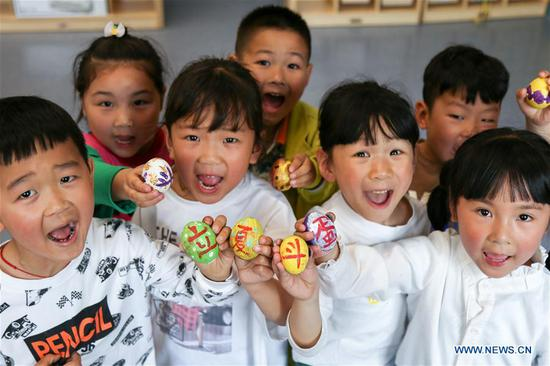 Children show painted eggs to mark the upcoming