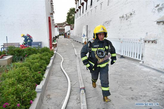 A firefighter runs in an emergency drill at the Potala Palace in Lhasa, southwest China's Tibet Autonomous Region, May 7, 2019. (Xinhua/Li Xin)