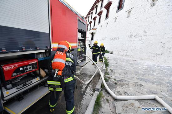 Firefighters connect fire hoses during an emergency drill at the Potala Palace in Lhasa, southwest China's Tibet Autonomous Region, May 7, 2019. (Xinhua/Li Xin)
