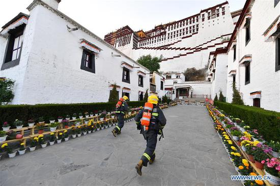 Firefighters run in an emergency drill at the Potala Palace in Lhasa, southwest China's Tibet Autonomous Region, May 7, 2019. (Xinhua/Li Xin)