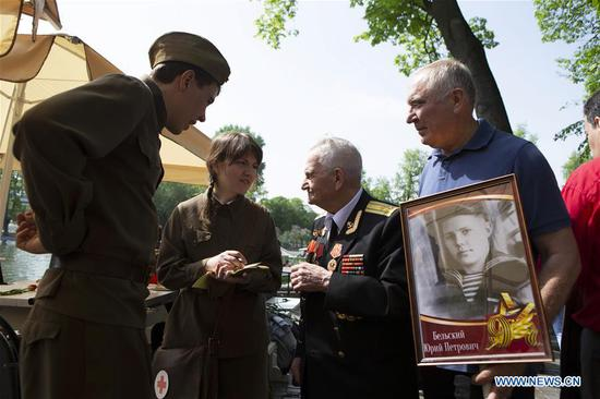 People dressed in Soviet-era uniforms talk with a World War II veteran during celebrations of the Victory Day in Moscow, Russia, on May 9, 2019. Russia marks the 74th anniversary of the victory over Nazi Germany in World War II here on May 9. (Xinhua/Alexander Zemlianichenko Jr)