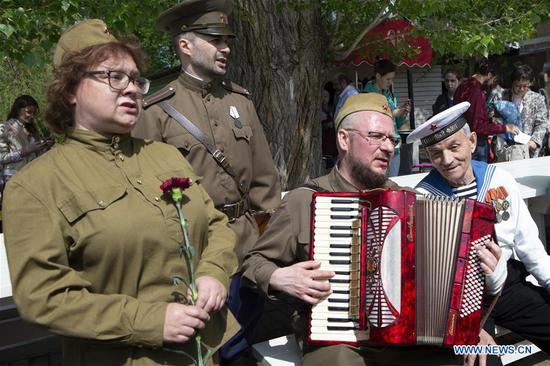 People dressed in Soviet-era uniforms sing with World War II veteran Victor Novopashin (R) during celebrations of the Victory Day in Moscow, Russia, on May 9, 2019. Russia marks the 74th anniversary of the victory over Nazi Germany in World War II here on May 9. (Xinhua/Alexander Zemlianichenko Jr)