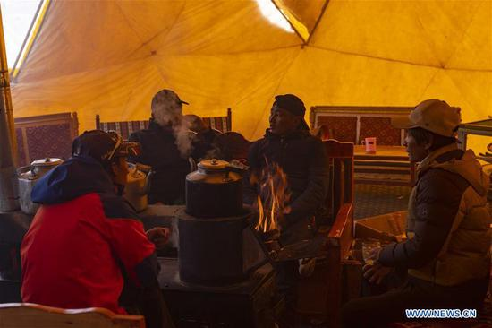 Climbers warm themselves in the tent of the Chinese mountaineering team at the base camp of the northern face of Mount Qomolangma in southwest China's Tibet Autonomous Region, April 25, 2019. Every year, for a few weeks, hundreds of climbers and supporting personnel come to the base camp of the northern face of Mount Qomolangma, trying to reach the summit of the tallest and most famous mountain in the world. Before starting climbing, they need to hike several times between elevations from 5,000 meters to 7,000 meters, giving their bodies some time to adapt. When this process is over, it's all up to the weather. The base camp is a popular place to wait for the window. Among the six camps on the northern face, the base camp at an altitude of 5,200 meters is the furthest cars can reach and therefor the most equipped. Besides food and accommodation, climbers can also enjoy tea and massage. They can also play football on perhaps the highest field. There's even a simple gym in the camp. Environmental protection is a priority here. Garbage sacks are given to each climbing team. Special containers are put in every camp to collect trash and sewage. The collected trash must be treated 100 kilometers away, and the only road is a zigzagging track. It is not trucks, but yaks that are generally used to make the journey. Actually yaks are vital on the mountain. Beyond the base camp, yak is the only reliable transport. (Xinhua/Sun Fei)
