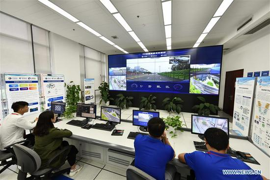 Researchers watch the data and image feedback during a test run for a remote-controlled car in Chongqing, southwest China, May 15, 2019. A remote-controlled car powered by the 5G network completed a test run on Wednesday in Chongqing. During the test run, a remote operator was able to control the car while watching the live feed of road conditions supported by the 5G network. (Xinhua/Liu Chan)
