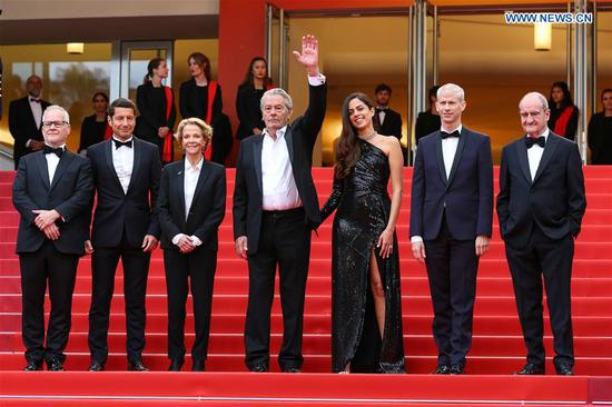 Actor Alain Delon (C) gestures with other guests at the premiere of the film