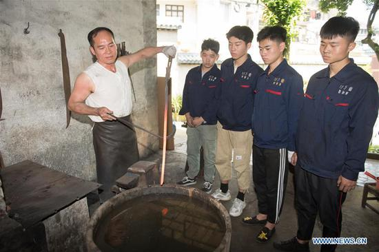 Zheng Guorong (L) teaches skills of sword making to his apprentices at Guyue Sword Studio in Longquan, east China's Zhejiang Province, May 21, 2019. For centuries, Longquan has been famed for its sword making industry. Zheng Guorong, 55, an intangible cultural heritage inheritor in Longquan Sword making, has been making sword for more than 30 years. Zheng regards sword as a symbol of spirit and devotes all to his career with awe. In his studio, the whole process of making a single sword takes two to three months, with steps including forming an idea, designing the sketch, preparing material and the final making and assembling. After setting up his studio, Zheng has trained more than 20 apprentices, who have all become sword smiths of great reputation. The old sword smith insists that Longquan sword, with a history of more than 2,500 years, deserves to be carried on in our time, both materially and spiritually. (Xinhua/Weng Xinyang)