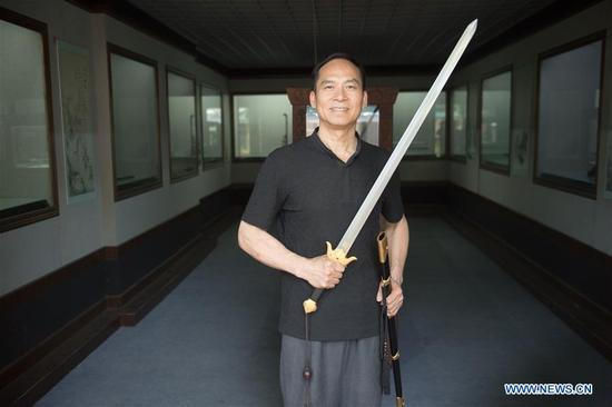 Zheng Guorong poses for a photo with a sword he made at Guyue Sword Studio in Longquan, east China's Zhejiang Province, May 21, 2019. For centuries, Longquan has been famed for its sword making industry. Zheng Guorong, 55, an intangible cultural heritage inheritor in Longquan Sword making, has been making sword for more than 30 years. Zheng regards sword as a symbol of spirit and devotes all to his career with awe. In his studio, the whole process of making a single sword takes two to three months, with steps including forming an idea, designing the sketch, preparing material and the final making and assembling. After setting up his studio, Zheng has trained more than 20 apprentices, who have all become sword smiths of great reputation. The old sword smith insists that Longquan sword, with a history of more than 2,500 years, deserves to be carried on in our time, both materially and spiritually. (Xinhua/Weng Xinyang)