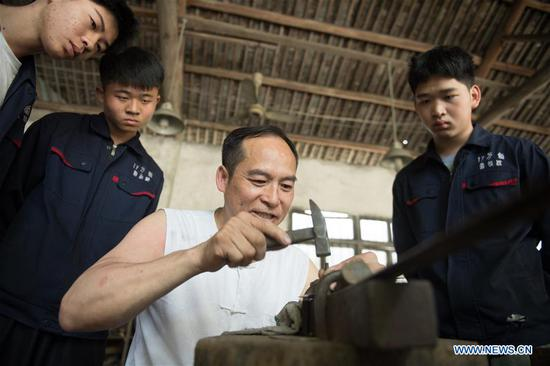 Zheng Guorong's apprentices watch him carving on a sword at Guyue Sword Studio in Longquan, east China's Zhejiang Province, May 21, 2019. For centuries, Longquan has been famed for its sword making industry. Zheng Guorong, 55, an intangible cultural heritage inheritor in Longquan Sword making, has been making sword for more than 30 years. Zheng regards sword as a symbol of spirit and devotes all to his career with awe. In his studio, the whole process of making a single sword takes two to three months, with steps including forming an idea, designing the sketch, preparing material and the final making and assembling. After setting up his studio, Zheng has trained more than 20 apprentices, who have all become sword smiths of great reputation. The old sword smith insists that Longquan sword, with a history of more than 2,500 years, deserves to be carried on in our time, both materially and spiritually. (Xinhua/Weng Xinyang)