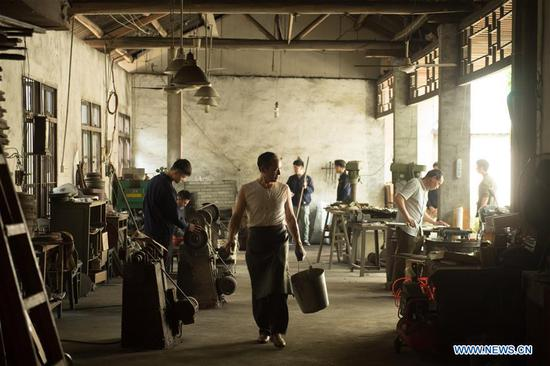 Zheng Guorong (C) and his apprentices work at Guyue Sword Studio in Longquan, east China's Zhejiang Province, May 21, 2019. For centuries, Longquan has been famed for its sword making industry. Zheng Guorong, 55, an intangible cultural heritage inheritor in Longquan Sword making, has been making sword for more than 30 years. Zheng regards sword as a symbol of spirit and devotes all to his career with awe. In his studio, the whole process of making a single sword takes two to three months, with steps including forming an idea, designing the sketch, preparing material and the final making and assembling. After setting up his studio, Zheng has trained more than 20 apprentices, who have all become sword smiths of great reputation. The old sword smith insists that Longquan sword, with a history of more than 2,500 years, deserves to be carried on in our time, both materially and spiritually. (Xinhua/Weng Xinyang)