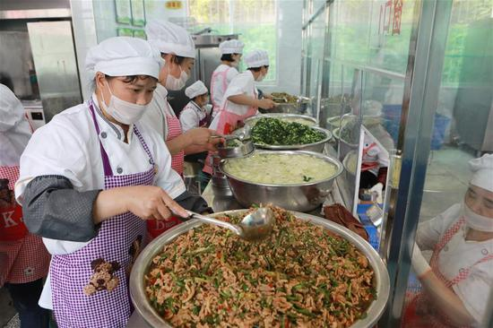 Staff members prepare lunch for students at No.11 Primary School of Tongren City in southwest China's Guizhou Province, May 21, 2019. Tongren City has established a monitoring system applying new technologies of big data to trace food from farming to dining table, an effort to guarantee food safety for students. (Xinhua/Ou Dongqu)