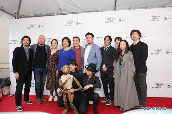 "Photo taken on April 28, 2019 shows Ma Liang (2nd L), S. Leo Chiang (5th L, rear), Sun Yang (5th R, rear), Paul Brill (4th R) and other crew members posing for a group photo on the red carpet during the premiere of Chinese documentary ""Our Time Machine"", in New York, the United States. ""Our Time Machine"" is a touching Chinese documentary which described how Ma, a renowned Chinese photographer and artist in Shanghai, got closer to his father, managed to stick to his creative career despite various challenges, and found the true meaning of life. (Xinhua/Luo Jingjing)"