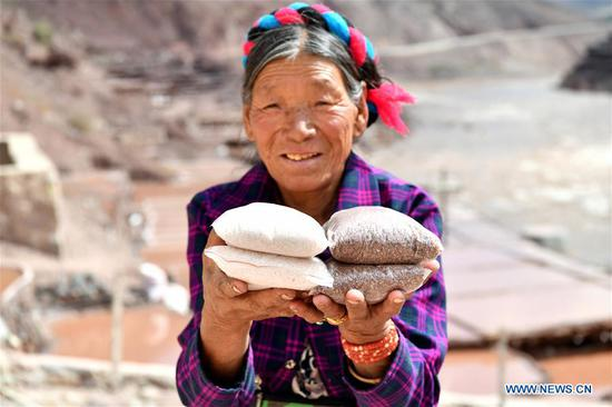 A villager shows salt products in Mangkam County, southwest China's Tibet Autonomous Region, May 22, 2019. An ancient technique of salt production since Tang Dynasty (618-907) is well-preserved in Mangkam County. Local people follow a salt harvesting method by collecting brines from salt mines and ponds and evaporating them in the sun until crystallization. (Xinhua/Li Xin)