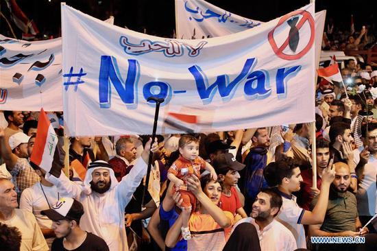 People hold anti-war banners and wave Iraqi flags during a protest in Baghdad, Iraq, on May 24, 2019. Hundreds of supporters of Iraqi prominent Shiite cleric Moqtada al-Sadr rallied on Friday evening in the capital Baghdad and other Iraqi cities, rejecting war between Iran and the United States. (Xinhua/Khalil Dawood)