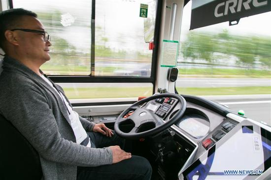 A staff member checks operating data during test drive of an auto-pilot passenger bus at the National Intelligent Connected Vehicle Pilot Zone in Changsha, central China's Hunan Province, April 28, 2019. China has established the world's most comprehensive new energy vehicle (NEV) supporting system, Huang Libin, spokesman with the Ministry of Industry and Information Technology, said at a recent news conference. During the first quarter, China's NEV production and sales amounted to 304,000 and 299,000 vehicles respectively, up 102.7 percent and 109.7 percent. (Xinhua/Chen Sihan)