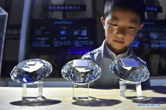 A kid views chips designed for 5G base stations by Huawei during China International Big Data Industry Expo 2019 in Guiyang, southwest China's Guizhou Province, May 26, 2019. The expo on big data opened Sunday in Guizhou Province, focusing on the latest innovation of the technology and its applications. The four-day expo will be attended by 448 enterprises from 59 countries and regions, according to the organizing committee. (Xinhua/Ou Dongqu)