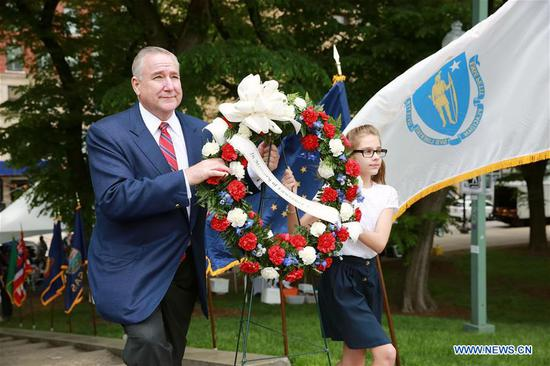 A military veteran and a girl lay wreath during a ceremony for Memorial Day in Chicago, the United States, on May 27, 2019. (Xinhua/Wang Ping)