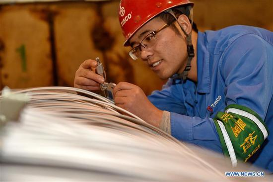 A staff member of Taiyuan Iron and Steel (Group), or TISCO, examines stainless steel wire for ballpoint pen tips making in Taiyuan, north China's Shanxi Province, Jan. 10, 2017. As a leading stainless steel maker, TISCO boasted research and development of high-tech stainless steel products by large efforts on innovation. So far TISCO possesses over 2,700 authorized patents, including 772 patents for invention. (Xinhua/Cao Yang)