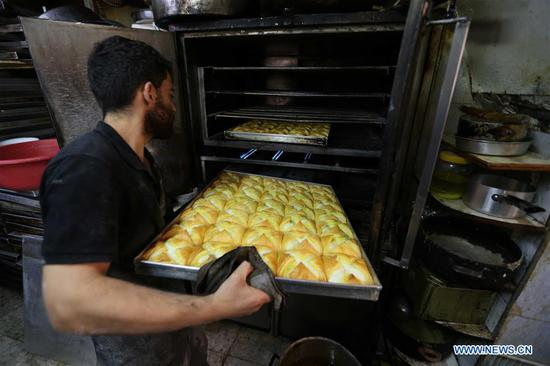 A worker prepares traditional cookies in Jerusalem's Old City ahead of Eid al-Fitr, marking the end of the holy month of Ramadan, on June 4, 2019. (Xinhua/Muammar Awad)