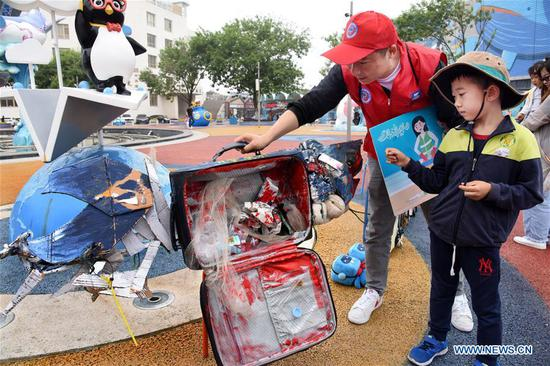 A volunteer introduces an art work made of ocean trash to a boy in Qingdao, east China's Shandong Province, June 5, 2019. A themed art exhibition was held at Haichang Ocean Park in Qingdao on Wednesday, to greet the upcoming World Oceans Day. (Xinhua/Li Ziheng)