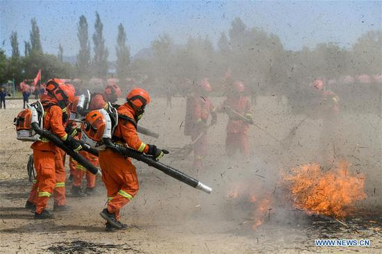 Newly-recruited firemen put out fire during a training in Hohhot, north China's Inner Mongolia Autonomous Region, June 5, 2019. Over 1,100 socially-recruited firemen are receiving a six-month training in Hohhot. (Xinhua/Peng Yuan)