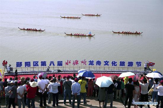 People watch a dragon boat race to celebrate the Dragon Boat Festival by the riverside of Hanjiang River in Yunyang District of Shiyan City, central China's Hubei Province, on June 6, 2019. The Dragon Boat Festival falls on the fifth day of the fifth month of the Chinese lunar calendar, or June 7 this year. (Xinhua/Cao Zhonghong)