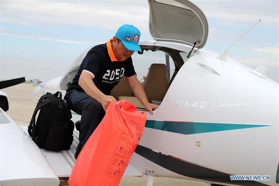 Zhang Bo unloads an immersion suit from his plane at an airport in Chicago, the United States, on June 9, 2019. After flying 68 days and making 50 stops, 57-year-old Bo Zhang completed his second around-the-world flight and landed in Chicago on Sunday morning. On April 2, Zhang kicked off the flight in the same airport in Chicago. In 68 days, he flied through 21 countries in three continents and over three oceans, with total mileage reaching 41,000 kilometers. (Xinhua/Wang Ping)