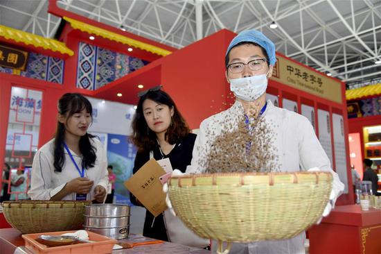 A staff member (R) works at a booth during the Global Health Forum (GHF) of Boao Forum for Asia (BFA) at Qingdao World Expo City in Qingdao, east China's Shandong Province, on June 10, 2019. Themed with