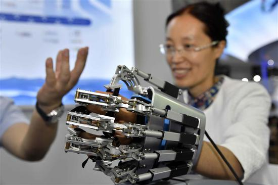 A visitor tries a medical device for hand rehabilitation during the Global Health Forum (GHF) of Boao Forum for Asia (BFA) at Qingdao World Expo City in Qingdao, east China's Shandong Province, on June 10, 2019. Themed with