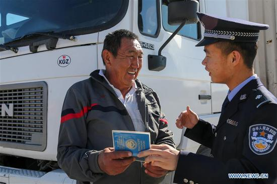 A driver from Kyrgyzstan talks to a policeman at a border inspection station of Irkeshtam port in northwest China's Xinjiang Uygur Autonomous Region on June 11, 2019. Irkeshtam is China's far west land port open to Kyrgyzstan. (Xinhua/Luo Yang)