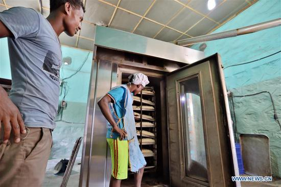 A baker uses baking oven in Adama, Ethiopia, June 11, 2019. Steady power supply was achieved since a Chinese-built power distribution, rehabilitation and upgrading project involving 8 Ethiopian cities was put into operation in March 2019. (Xinhua/Wang Teng)