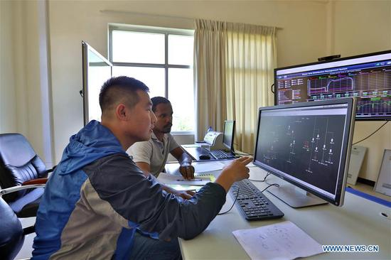 Guo Yongqiang, a staff member of China Electric Power Equipment and Technology Co., Ltd (CET), guides a local employee at the grid control center in Adama, Ethiopia, June 11, 2019. Steady power supply was acheived since a Chinese-built power distribution, rehabilitation and upgrading project involving 8 Ethiopian cities was put into operation in March 2019. (Xinhua/Wang Teng)