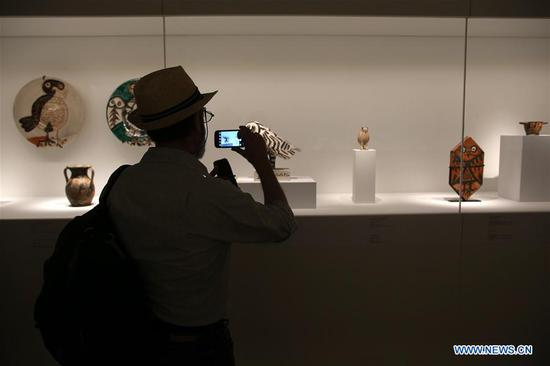 "A visitor takes photos at the media preview of ""Picasso and Antiquity. Line and Clay"" at the Museum of Cycladic Art in Athens, Greece, June 19, 2019. A rare exhibition about Pablo Picasso and his inspiration from ancient Greek art is to open here at the Museum of Cycladic Art on Thursday. (Xinhua/Marios Lolos)"