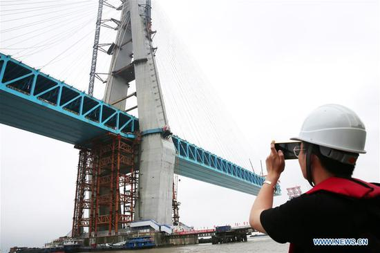 A worker takes a picture of the south main tower of a Yangtze River bridge on the Shanghai-Nantong railway line in Nantong, east China's Jiangsu Province, June 27, 2019. The south main tower of the bridge was completed on Thursday, marking an important progress of the construction of the cable-stayed railway-expressway bridge. (Xinhua/Xu Congjun)