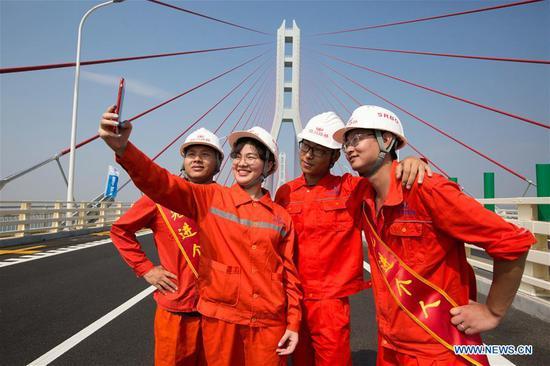 Constructors of the Poyang Lake No. 2 Bridge take selfies on the bridge in east China's Jiangxi Province, June 28, 2019. The 5.589-km Poyang Lake No. 2 Bridge, which links Duobao Township of Duchang County and Hualin Township of Lushan City in Jiangxi Province, opened to the public traffic on Friday. (Xinhua/Fu Jianbin)