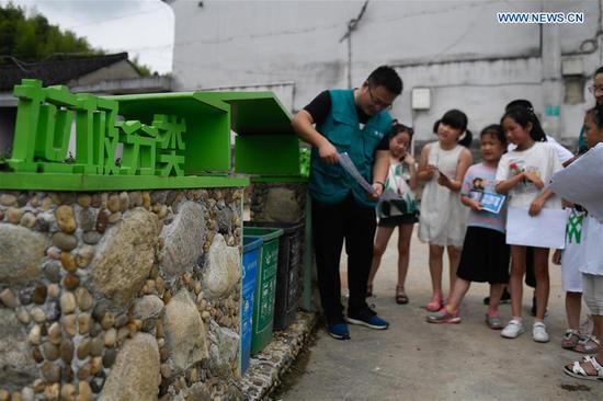 A vounlteer (L) shares knowledge of garbage sorting with students at Jianling Village in Dayan Township of Ningbo City, east China's Zhejiang Province, June 30, 2019. Jianling has been chosen to be a pilot village in Nov. 2018 for practising garbage processing in Dayan Township. (Xinhua/Huang Zongzhi)
