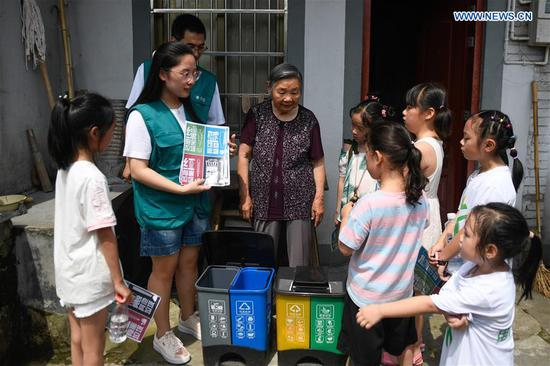 A vounlteer (2nd L) shares knowledge of garbage sorting with locals at Jianling Village in Dayan Township of Ningbo City, east China's Zhejiang Province, June 30, 2019. Jianling has been chosen to be a pilot village in Nov. 2018 for practising garbage processing in Dayan Township. (Xinhua/Huang Zongzhi)