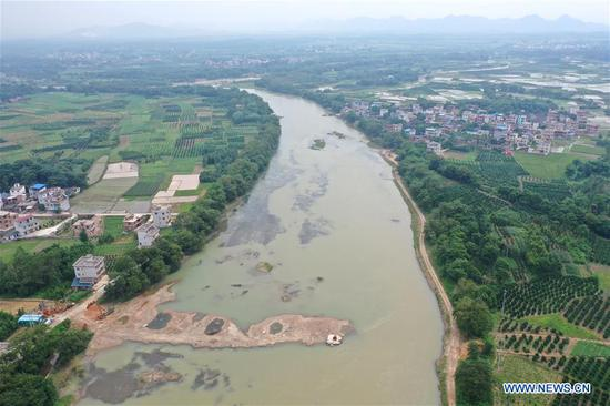 Aerial photo taken on June 29, 2019 shows a bridge under construction near a historical site of the 1934 Battle of Xiangjiang in Quanzhou County, south China's Guangxi Zhuang Autonomous Region. The Battle of Xiangjiang in late 1934 is deemed by history experts as pivotal to a successful Long March of the Red Army led by the Communist Party of China (CPC) between 1934 and 1936. During the battle, the Red Army lost almost two thirds of its troops when crossing the Xiangjiang River from ferry points scattered in today's Guangxi Zhuang Autonomous Region, but managed to break through a military blockade line by the rival. By noon time on December 1, 1934, the main forces of the Red Army had all crossed the Xiangjiang River and the historic Long March was thus carried on. (Xinhua/Zhou Hua)