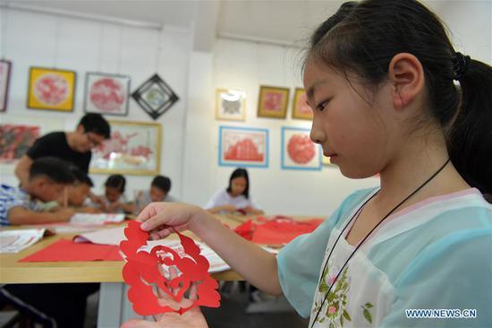 Children make papercutting works in Xin'gan County, east China's Jiangxi Province, July 3, 2019. Xin'gan papercutting is listed as a national intangible cultural heritage. (Xinhua/Peng Zhaozhi)