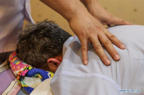 A guest experiences a massage therapy during a traditional Chinese medicine tour on the sidelines of the Annual Meeting of the New Champions 2019, or Summer Davos, in Dalian, northeast China's Liaoning Province, July 3, 2019. (Xinhua/Pan Yulong)